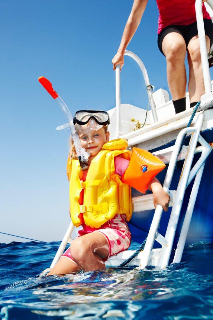 Kleines Kind klettert mit Schwimmweste und Schnorchel die Leiter vom Boot herunter.