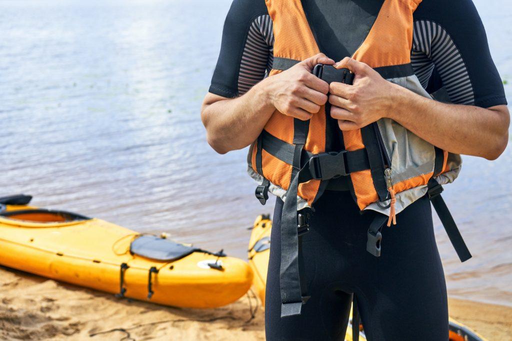 Mann am Gewässer zieht sich orangene Schwimmweste an.