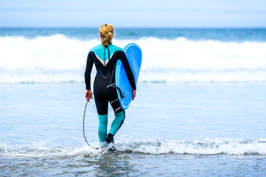 Frau am Strand mit blau-schwarzem Neoprenanzug und Surfbrett.