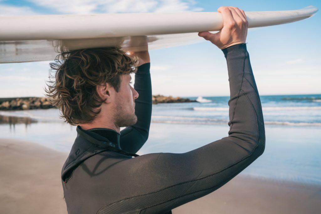 Mann im Neoprenanzug, der ein Surfbrett auf dem Kopf trägt.