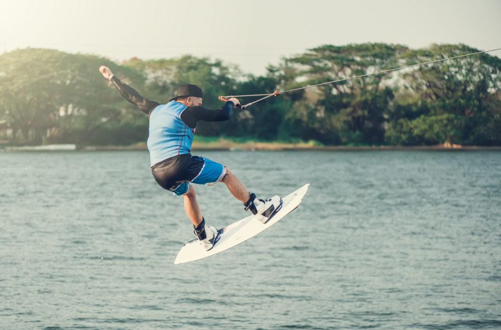 Wakeboarder springt über Wasser